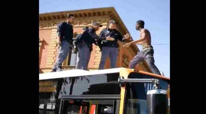 Italští policisté se snaží dostat Afričana ze střechy autobusu (video)